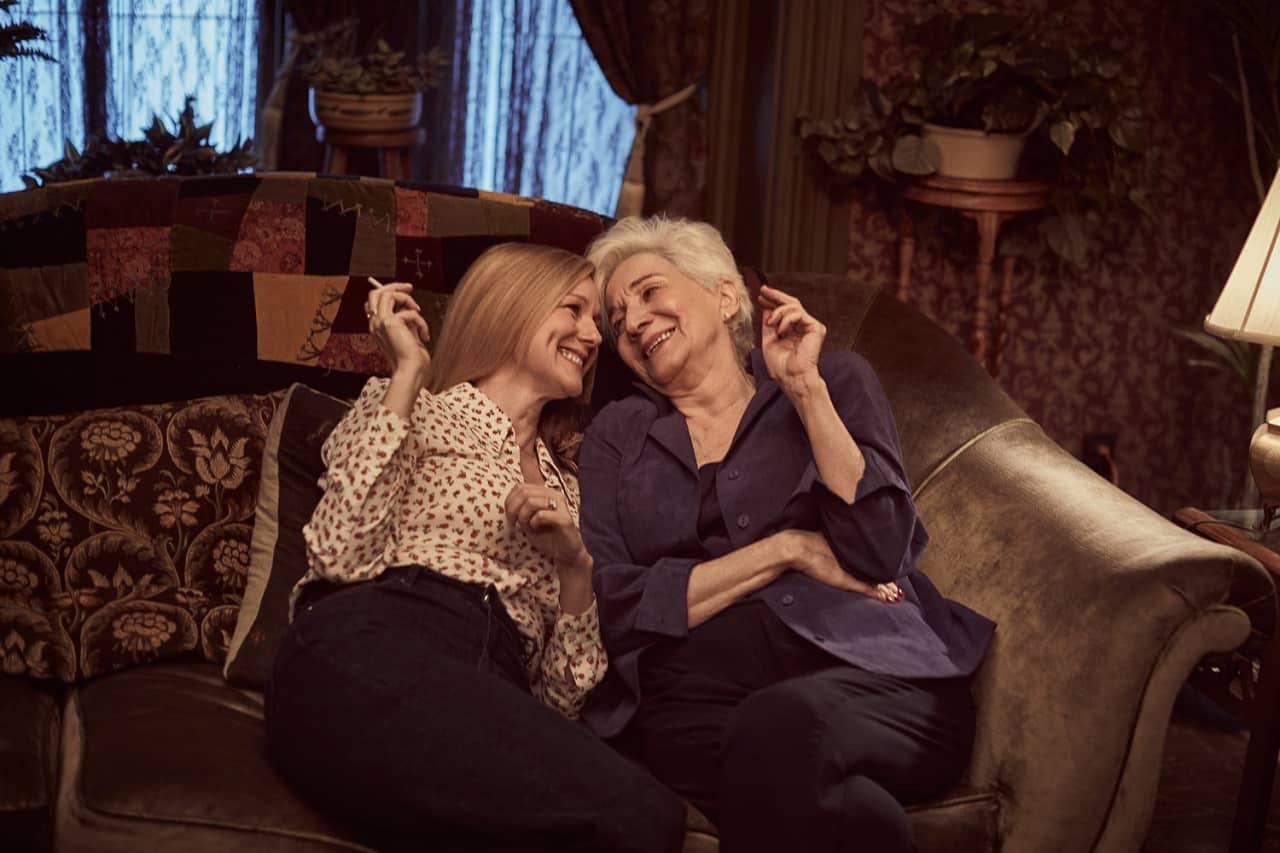 Laura Linney e Olympia Dukakis sono sedute vicine su divano. Si guardano e ridono. Hanno entrambe in mano una sigaretta.